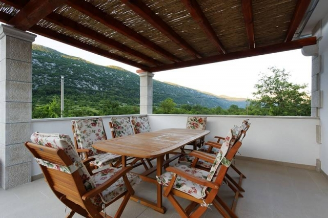 Covered terrace on the upper floor with the dining table and mountain view