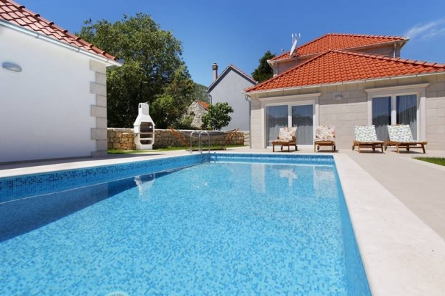 Swimming pool with sunbeds and open fireplace in the yard of the Villa Zupa